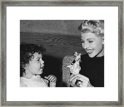Rita Hayworth Playing With Young Girl Framed Print