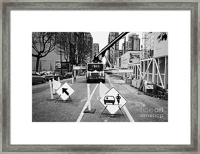 road closed to traffic to allow large articulated crane operate at building site Vancouver BC Canada Framed Print by Joe Fox