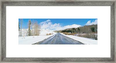 Road Through Snow Covered Countryside Framed Print