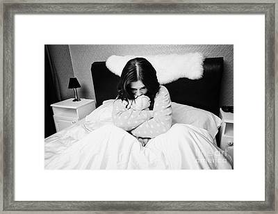 Sad Early Twenties Woman Holding Cuddly Dog Soft Toy In Bed In A Bedroom Framed Print