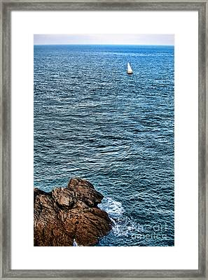 Sailboat Along Rocky Coastline Framed Print by Olivier Le Queinec