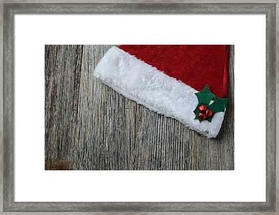 Santa Hat On Rustic Wood Background Framed Print by Brandon Bourdages