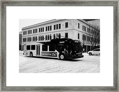 Saskatoon Transit Bus Travelling Through Snow Covered Downtown Streets Saskatchewan Canada Framed Print by Joe Fox