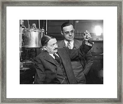 Scientists Look At Test Tube Framed Print by Underwood Archives