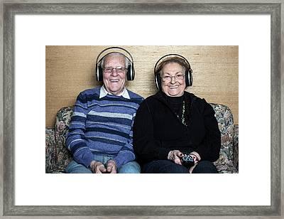 Senior Couple Wearing Headphones Framed Print