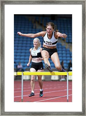 Senior Female Athlete Clears Hurdle Framed Print by Alex Rotas