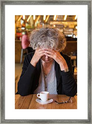 Senior Woman In Cafe With Head In Hands Framed Print