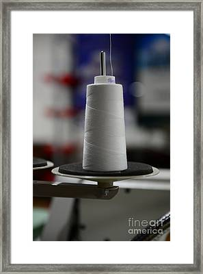 Sewing A Large Spool Of White Thread Framed Print by Paul Ward