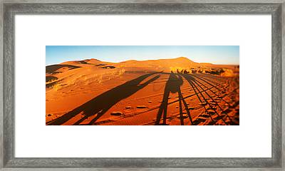 Shadows Of Camel Riders In The Desert Framed Print
