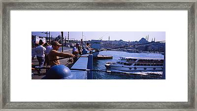 Side Profile Of Fishermen Fishing Framed Print by Panoramic Images