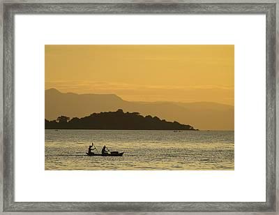 Silhouette Of Fishermen In Dugout Canoe Framed Print