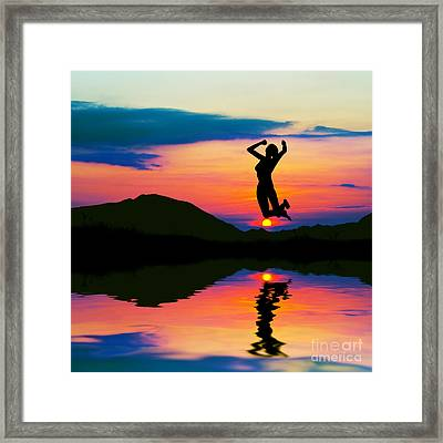 Silhouette Of Happy Woman Jumping At Sunset Framed Print