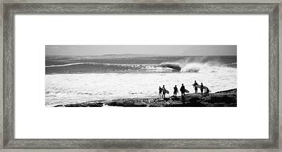 Silhouette Of Surfers Standing Framed Print by Panoramic Images