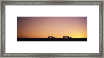 Silhouette Of Two Trucks Moving Framed Print