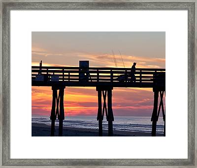 Silhouetted Fisherman On Ocean Pier At Sunrise Framed Print