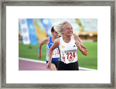 Silver-haired Female Athlete Running Framed Print by Alex Rotas