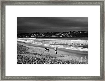 Single Woman Out Walking Her Dog On Ballycastle Beach In Winter County Antrim Northern Ireland Framed Print by Joe Fox