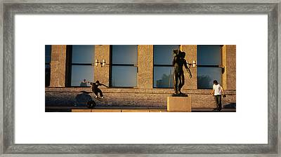 Skateboarders In Front Of A Building Framed Print by Panoramic Images
