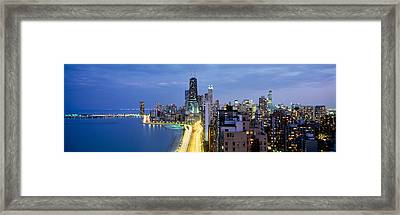 Skyscrapers Lit Up At The Waterfront Framed Print by Panoramic Images