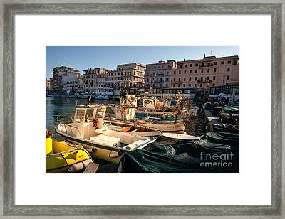 small working fishing boats moored stern first in Anzio harbour Framed Print