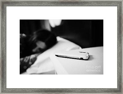 Smartphone On Bedside Table Of Early Twenties Woman In Bed In A Bedroom Framed Print