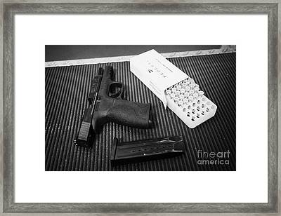 Smith And Wesson 9mm Handgun With Ammunition At A Gun Range Framed Print by Joe Fox