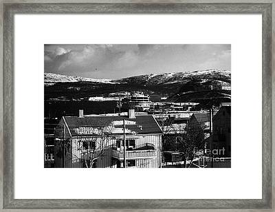 Snow Covered Street Of Traditional Wooden Houses Looking Down To Hurtigruten Ship In Kirkenes Harbou Framed Print
