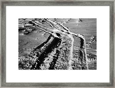 snowmobile tracks in snow across frozen field Canada Framed Print