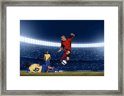 Soccer Player Jumping With Ball Framed Print by Kycstudio
