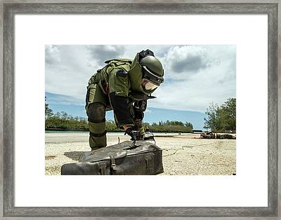 Soldier Dressed In Bomb Suit Inpecting Framed Print
