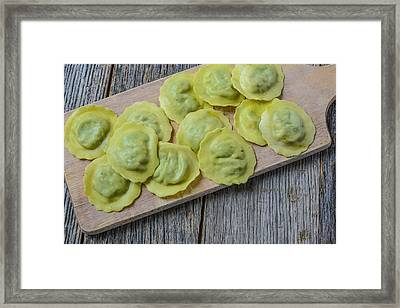Spinach Ravioli On A Wood Cutting Board Framed Print