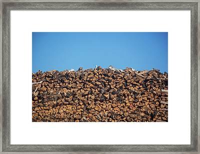Stack Of Firewood Pile Against Blue Sky Framed Print