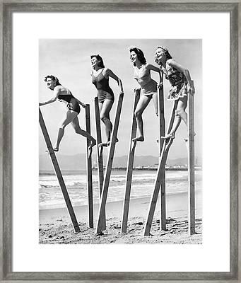 Stilt Walking On The Beach Framed Print by Underwood Archives