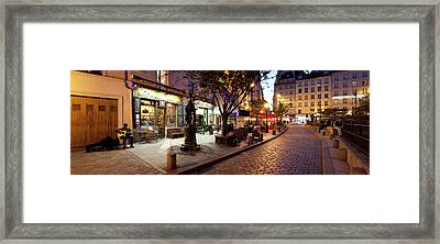 Stores At Dusk, Paris, Ile-de-france Framed Print by Panoramic Images