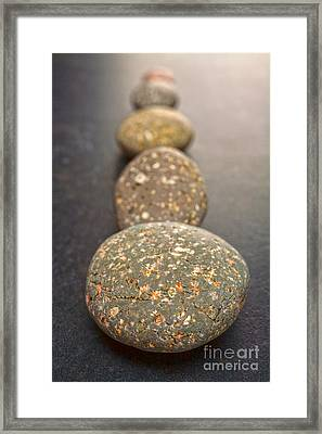 Straight Line Of Speckled Grey Pebbles On Dark Background Framed Print by Colin and Linda McKie