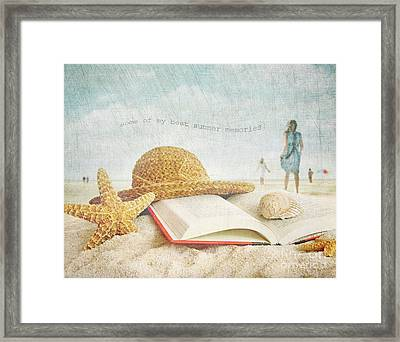 Straw Hat And Book In The Sand Framed Print by Sandra Cunningham