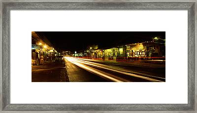 Streaks Of Lights On The Road In A City Framed Print by Panoramic Images