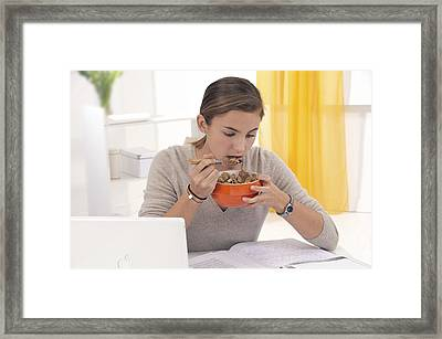Student Eating Cereal Framed Print by Science Photo Library