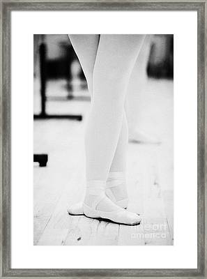 Students With Feet In The Third Position At A Ballet School In The Uk Framed Print by Joe Fox
