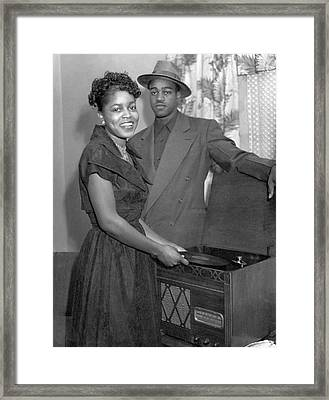 Stylish Couple Playing Records Framed Print by Underwood Archives