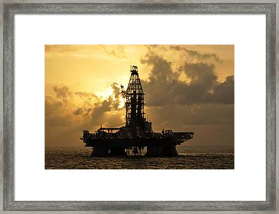 Sun Behind Oil Rig With Clouds Framed Print by Bradford Martin