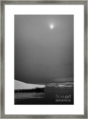 sun breaking through mist and cloud over snow covered ice shelf falling into the sea at Fournier Bay Framed Print
