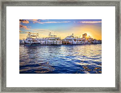 Sunset Over The Harbor Framed Print by Debra and Dave Vanderlaan