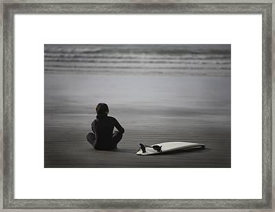 Surfer Sitting On Beach, Cox Bay Near Framed Print