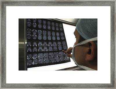 Surgeon Looking At Brain Scans Framed Print by Science Photo Library