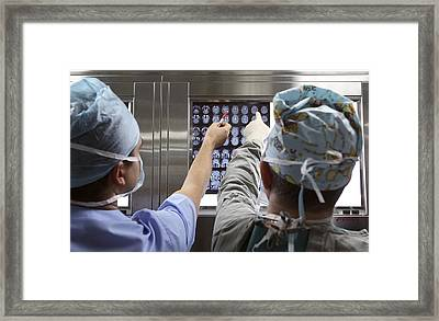 Surgeons Looking At Brain Scans Framed Print by Science Photo Library