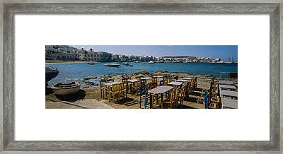Tables And Chairs In A Cafe, Greece Framed Print