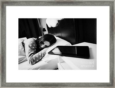 Tablet Computer On Bedside Table Of Early Twenties Woman In Bed In A Bedroom Focus On Woman Framed Print by Joe Fox