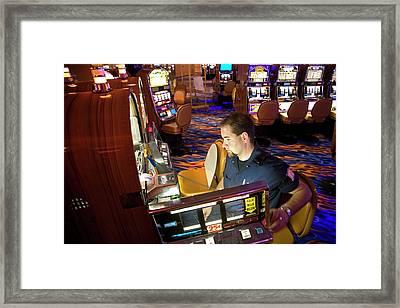 Technician Servicing A Slot Machine Framed Print by Jim West