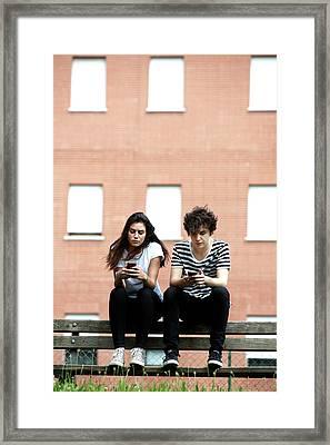 Teenage Couple Using Smart Phones Framed Print